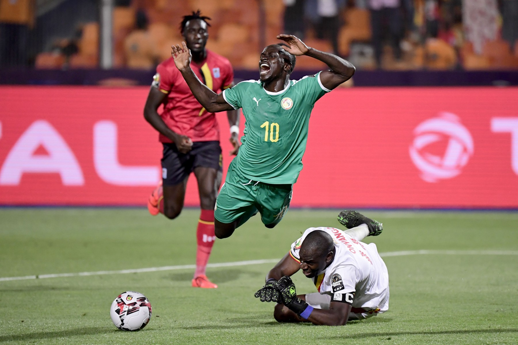 Uganda's goalkeeper Denis Onyango (below) fouls Senegal's forward Sadio Mane (C) during the 2019 Africa Cup of Nations (CAN) Round of 16 football match between Uganda and Senegal at the Cairo International Stadium in the Egyptian capital on July 5, 2019. (Photo by JAVIER SORIANO / AFP)