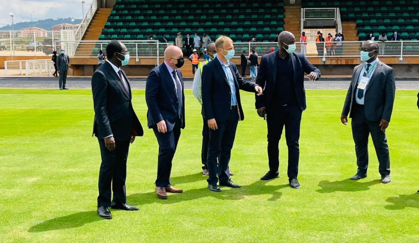 Les experts de la CAF et de la FIFA apprécient la qualité de la pelouse d'un terrain d'entraînement.